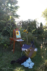 picture of painting easel with partially completed painting, set up  outdoors in garden.
