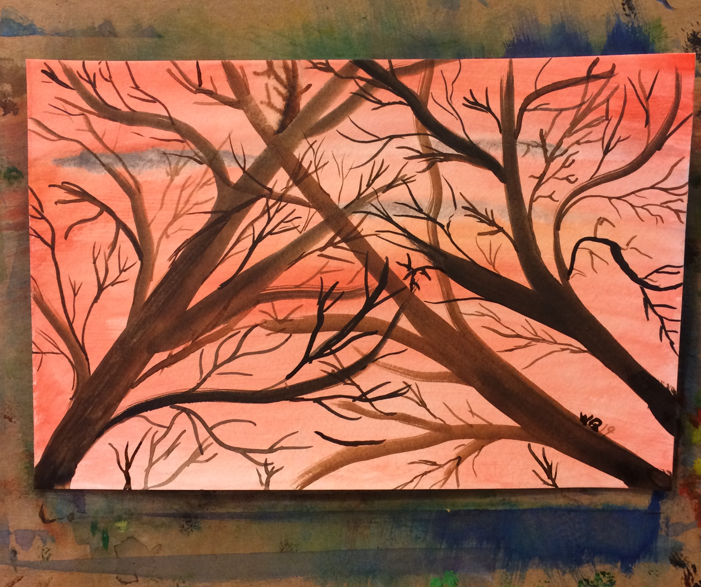 watercolour of red sunset with tree branches in front filling the page.