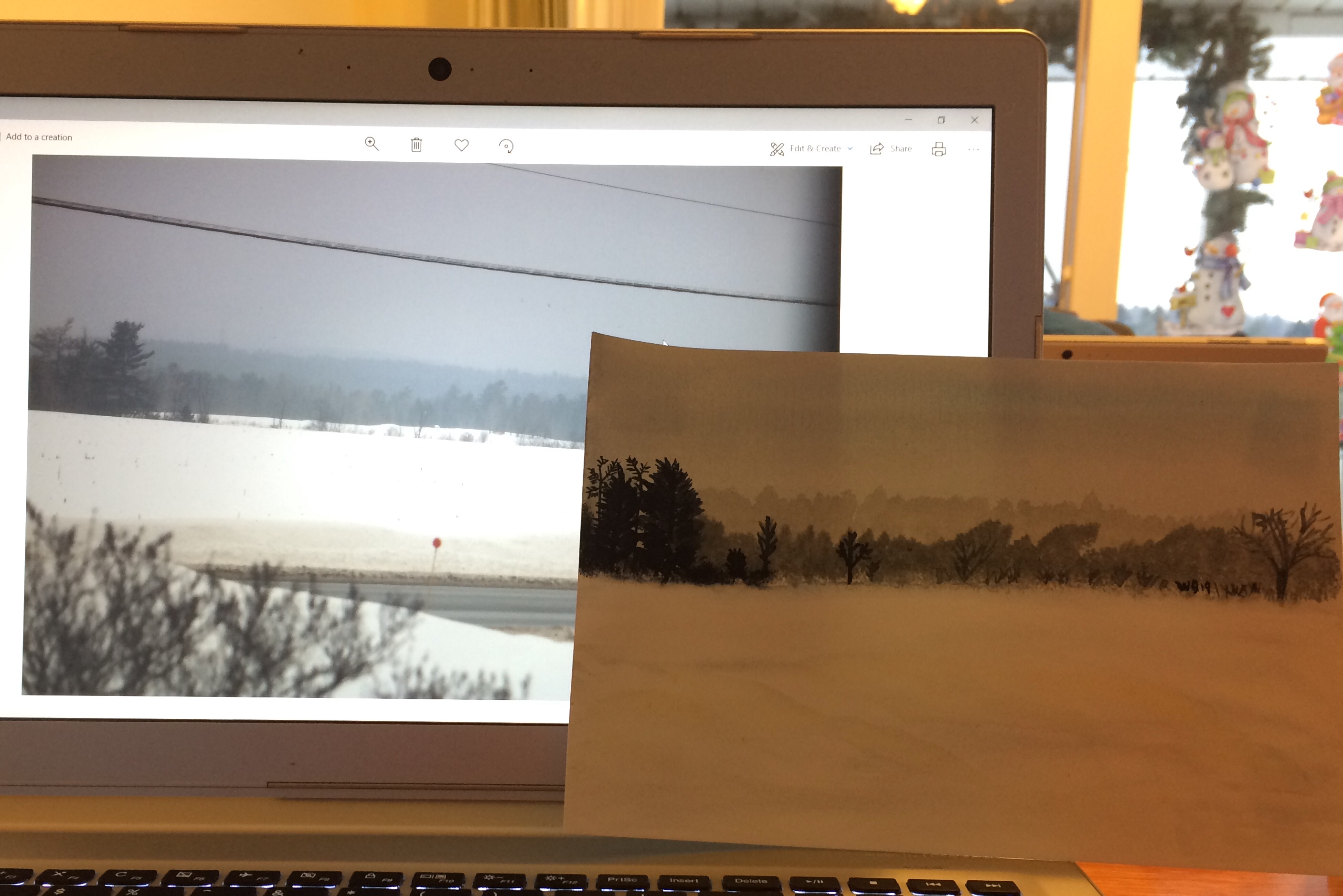 landscape photo of trees and a field of snow is displayed on a laptop screen with a watercolour painting of the photo.