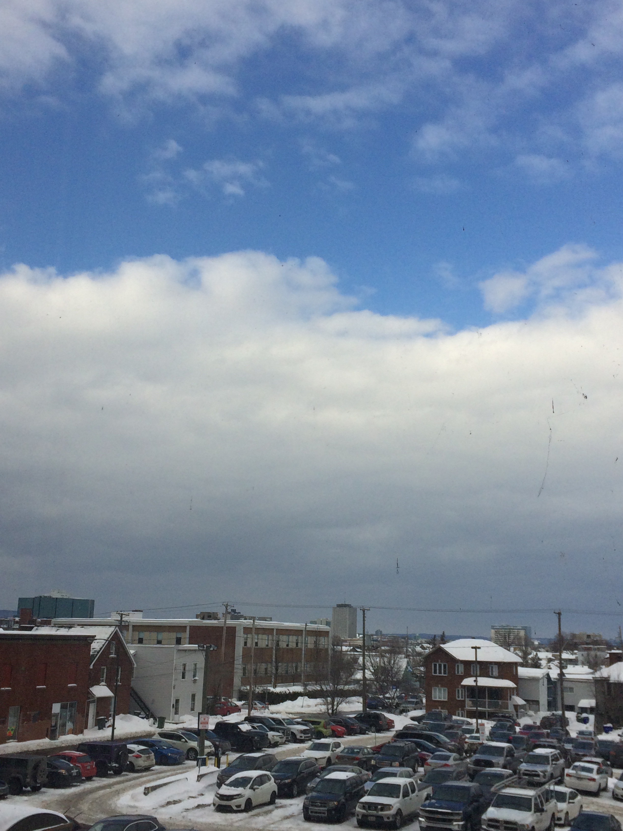 photo of blue sky, white clouds and a city street and parking lot