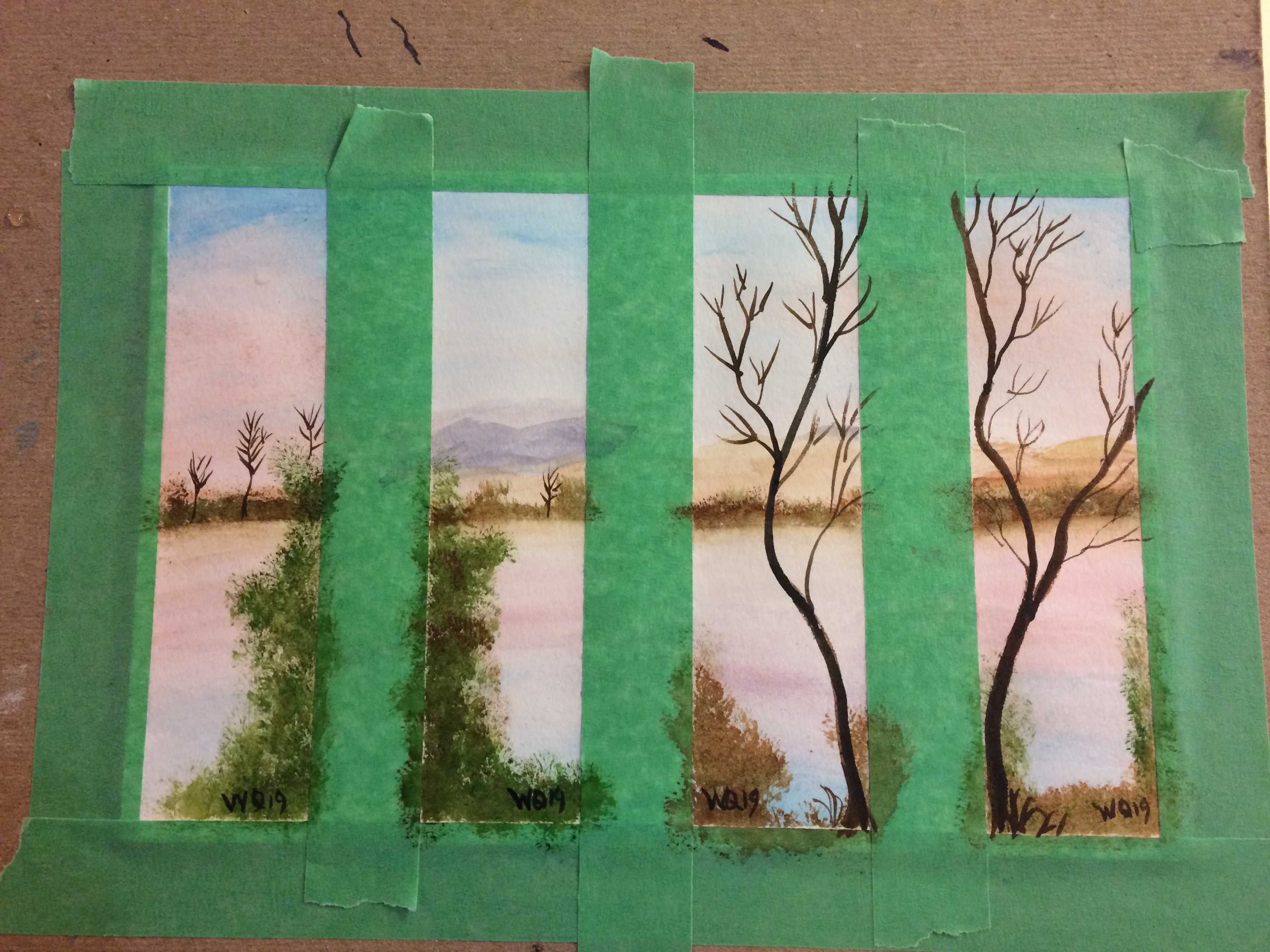 watercolour paper taped in four parts with a painting in each part of landscape: sky, water, trees.