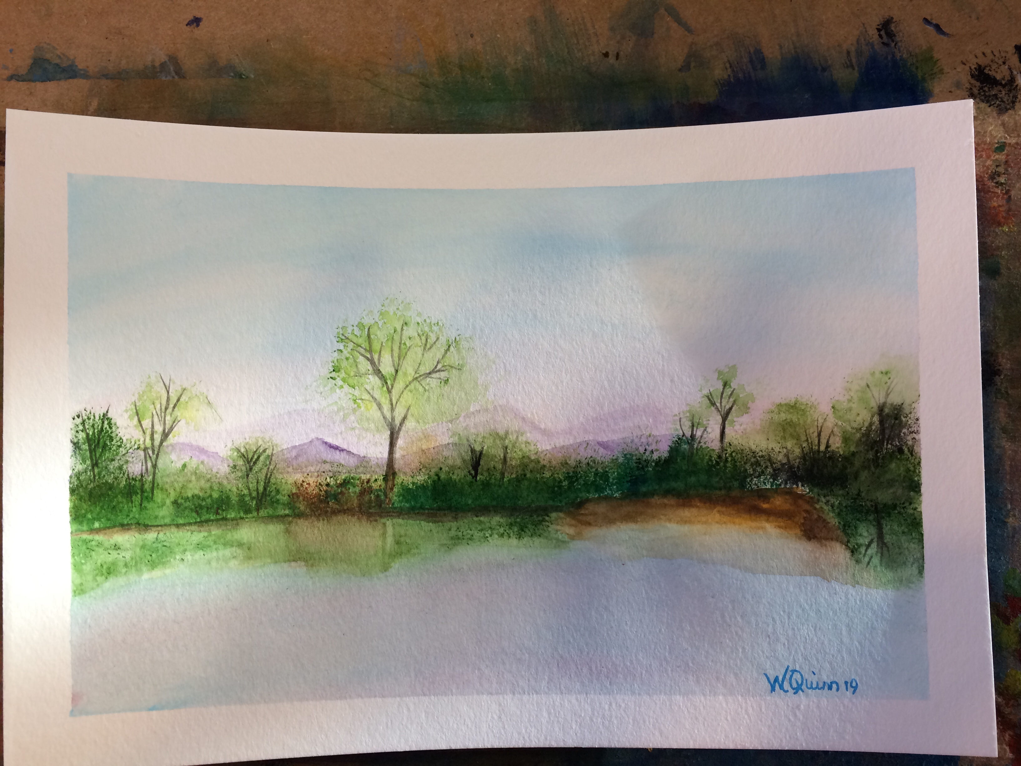 watercolour painting landscape blue sky, purple mountains in distance with bush and trees in forefront reflected in water.
