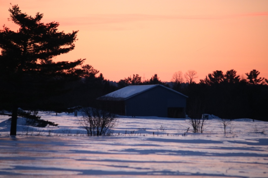 Photo of barn and a field of snow in the orange glow of sunset