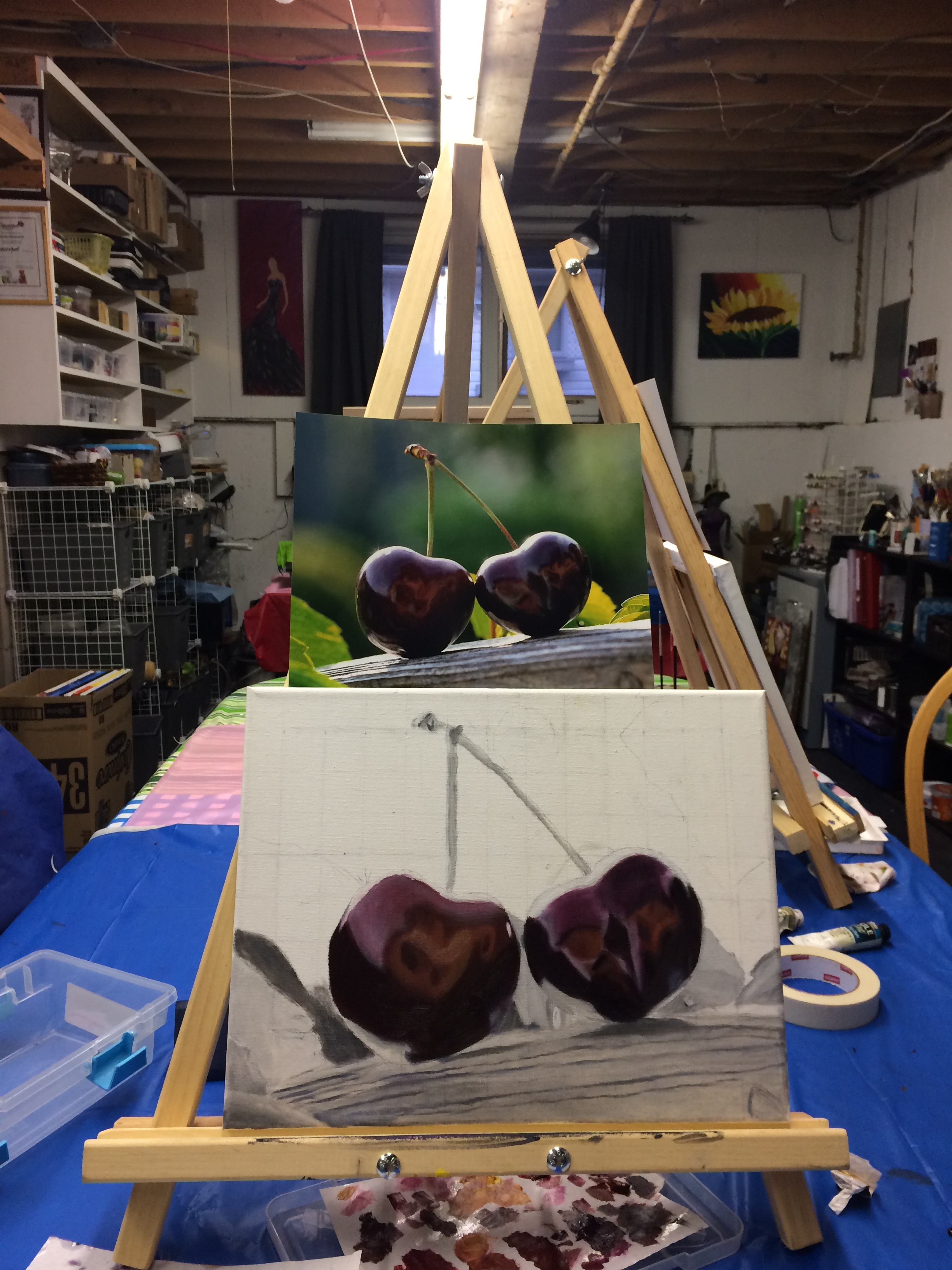 photo of oil painting of cherries in progress on easel with reference photograph above the painting.
