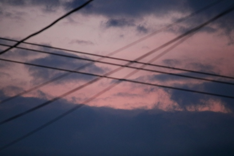 Close up of Small opening in the clouds reveals pink sunset