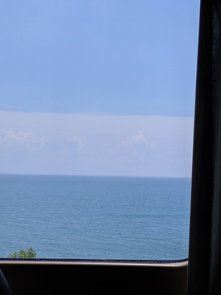 Photo out of train window of Lake Ontario and sky