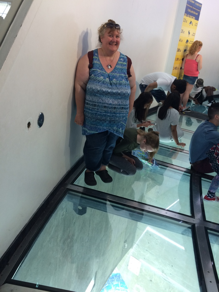 Woman posing while standing on glass floor in CN Tower