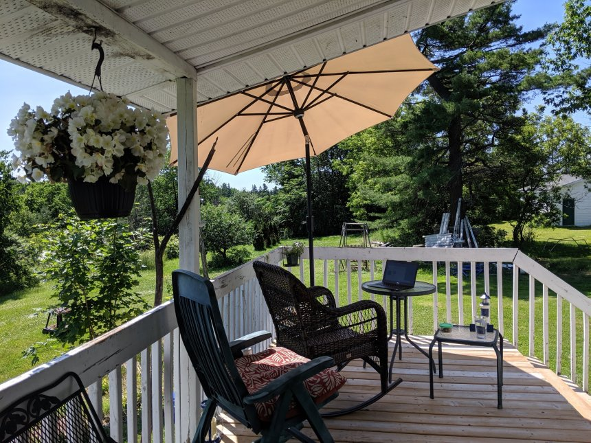 Outdoor patio with umbrella and laptop