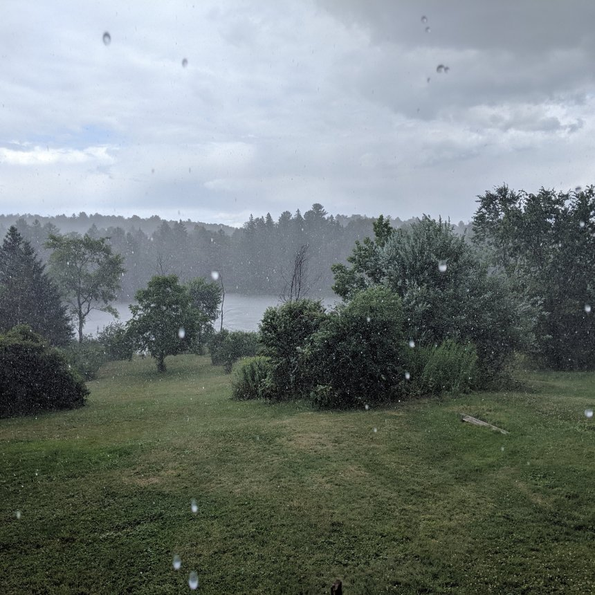 Landscape of yard and river with heavy rain drops falling