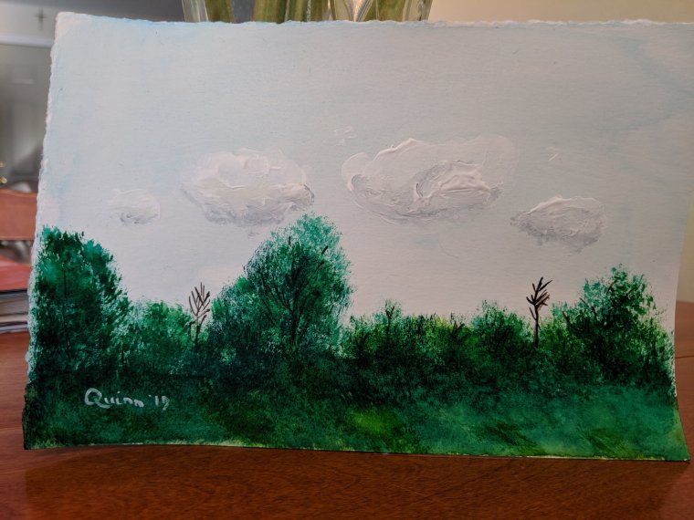 Watercolour blue sky with white clouds and tips of green trees