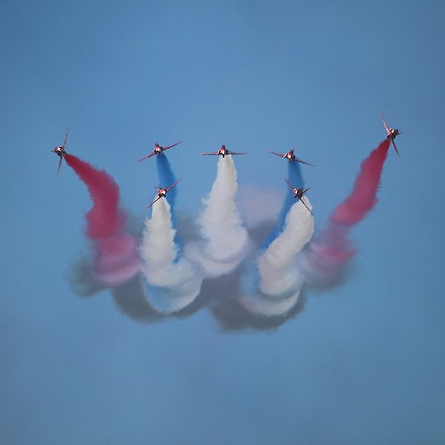 Planes in aerobatic maneuvers with red, blue and white smoke trailing