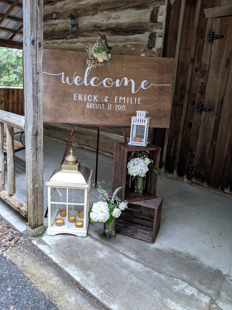Wooden sign with white lettering: Emilie and Erick's wedding