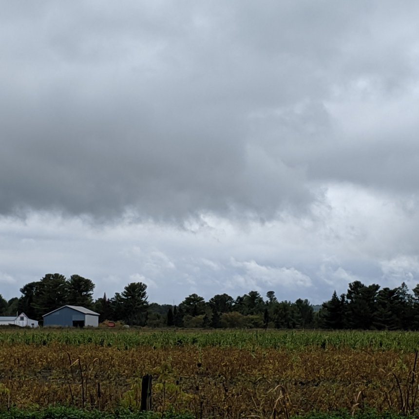 Photo landscape dark clouds over grey clouds with field and farm in shot