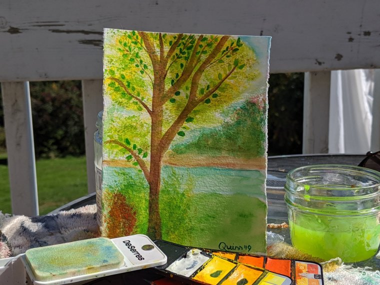 Watercolour painting tree with yellow and green leaves, shrubs around it and river behind it