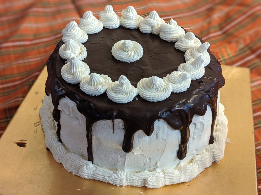 Cake decorated with white icing and chocolate ganache