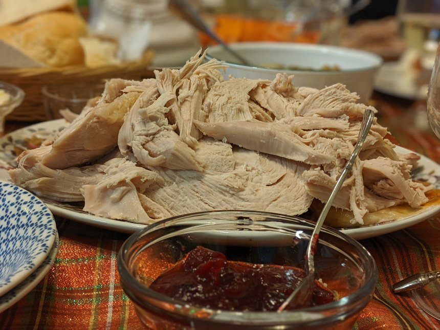 Table set with platter of turkey and serving bowl of cranberries