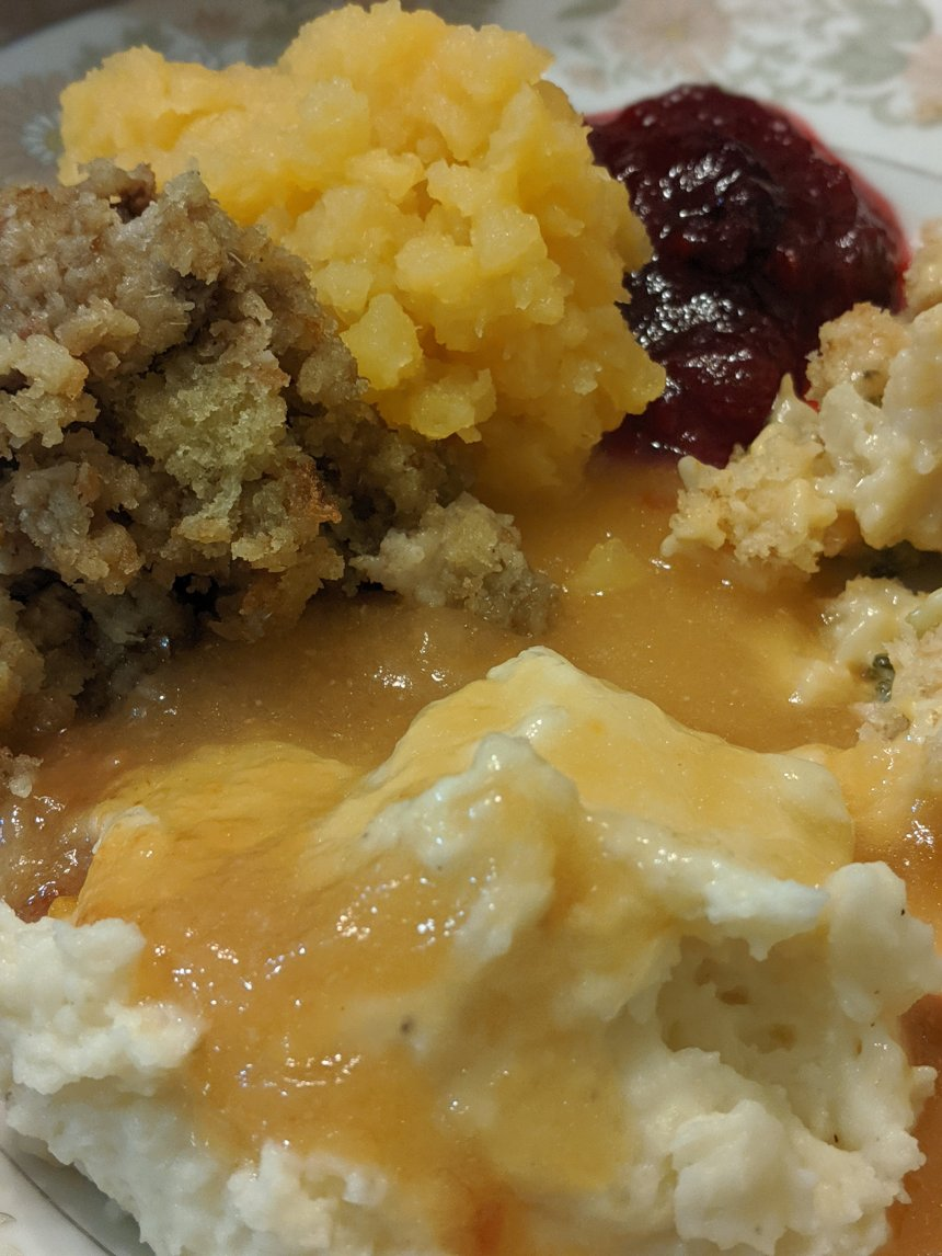 Plate of turkey, mashed potatoes and gravy, turnips, coleslaw, dressing and cranberries