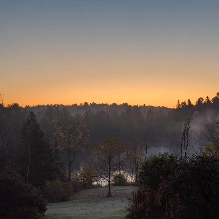 Sunrise over river with steam rising with green frosty grass sloping to river and trees in full autumn colours