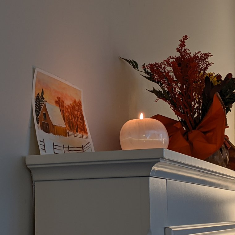 Candle burning in white ball of selenite on mantel of electric fireplace, flower piece with orange red flowers and watercolor painting in background of orange sunset, fall orange leaves and snow around a barn