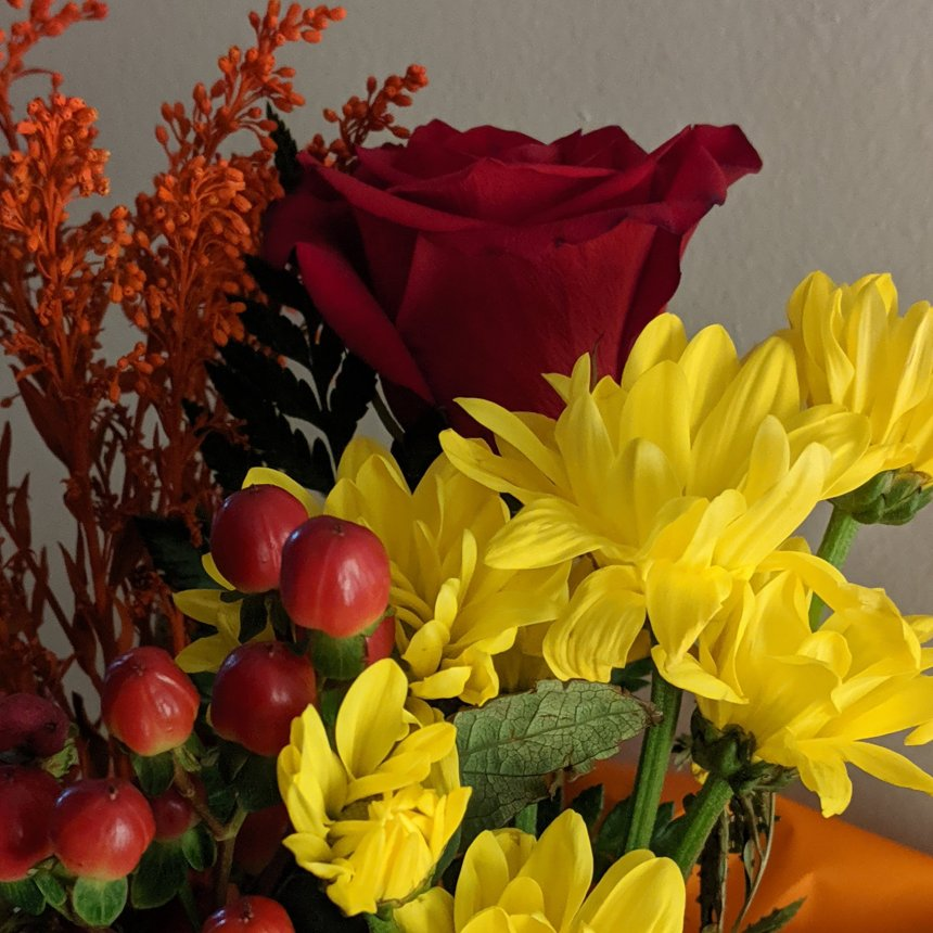 Red rose with yellow and red flowers in a bouquet