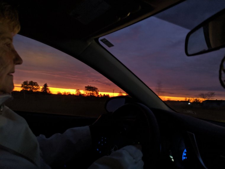 Woman driving car with sunrise beside her