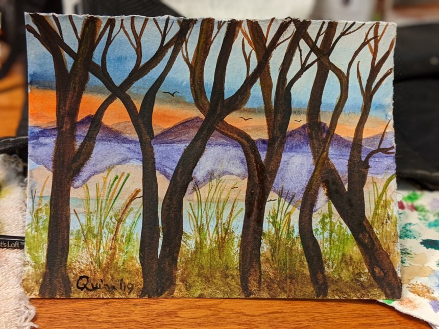 Watercolour painting orange sunset with dark blue sky overhead, purple mountains reflecting in water with brown bare trees and branches in the foreground