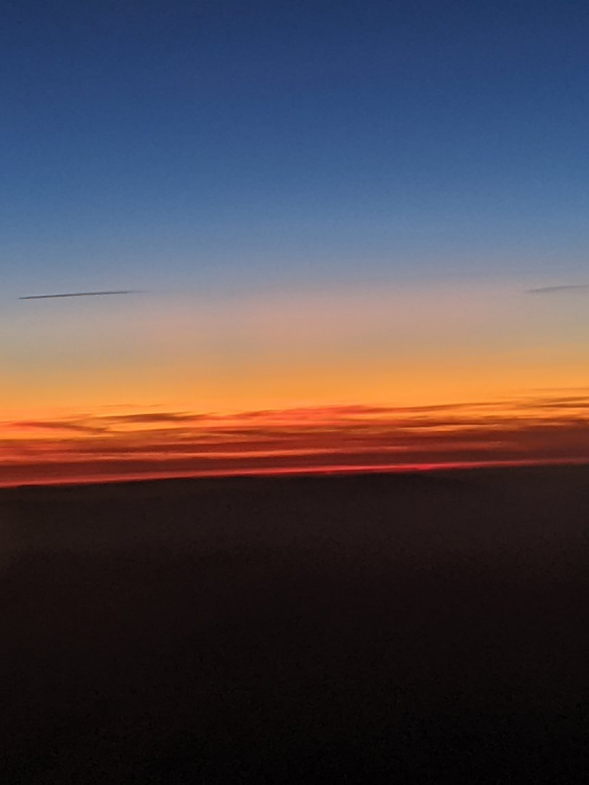 Sunset photo: blue sky on high fades into yellow then a glorious fire orange which touches the blackness of the earth.