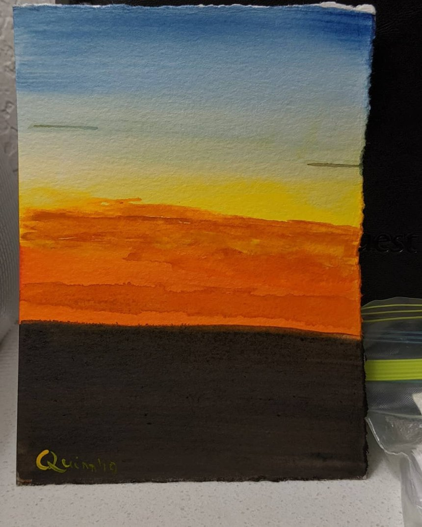 Watercolour painting sunset, blue sky on high fades into yellow then a glorious fire orange which touches the blackness of the earth.