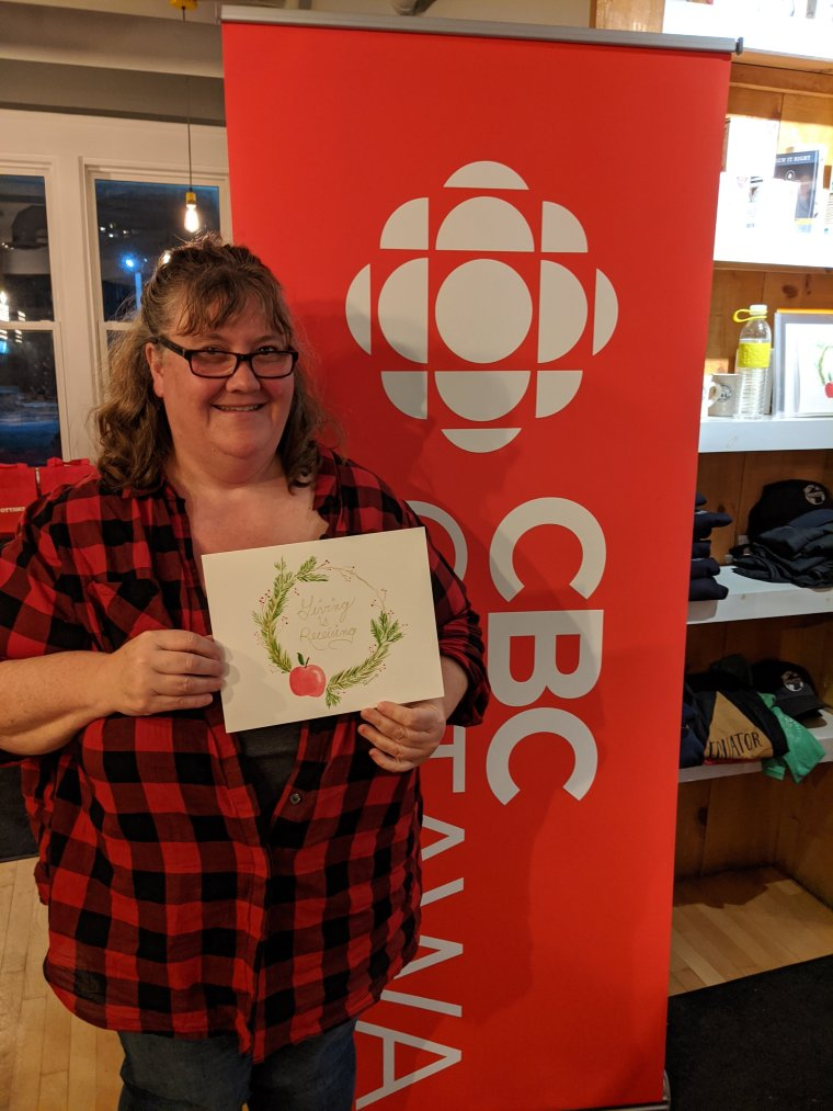 Author holding painting in front of CBC Ottawa sign