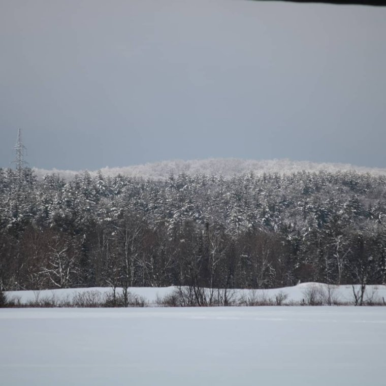 Snow covered hills in distance.