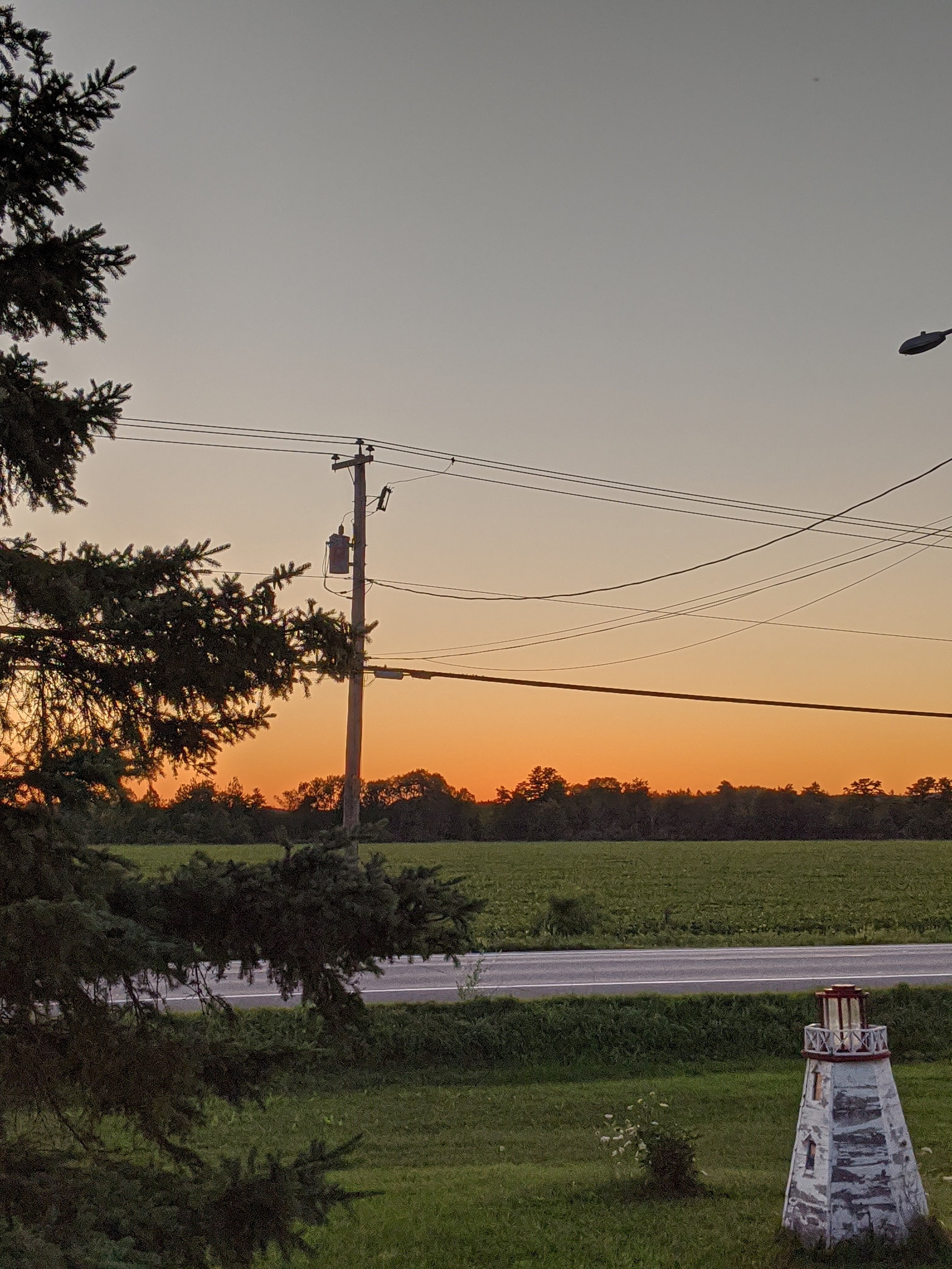 orange sunset glow over a country field and a yard with a lighthouse lawn ornament and large spruce tree