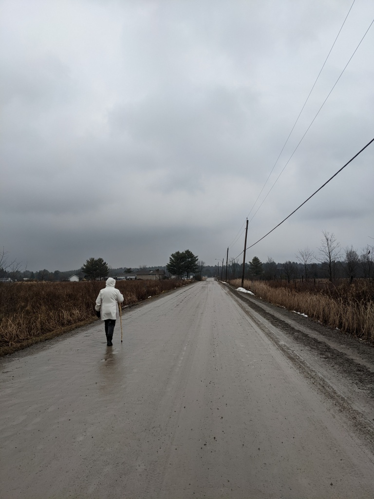 woman with walking stick walks on a wet, dirt, country road on a cloudy, rainy day.