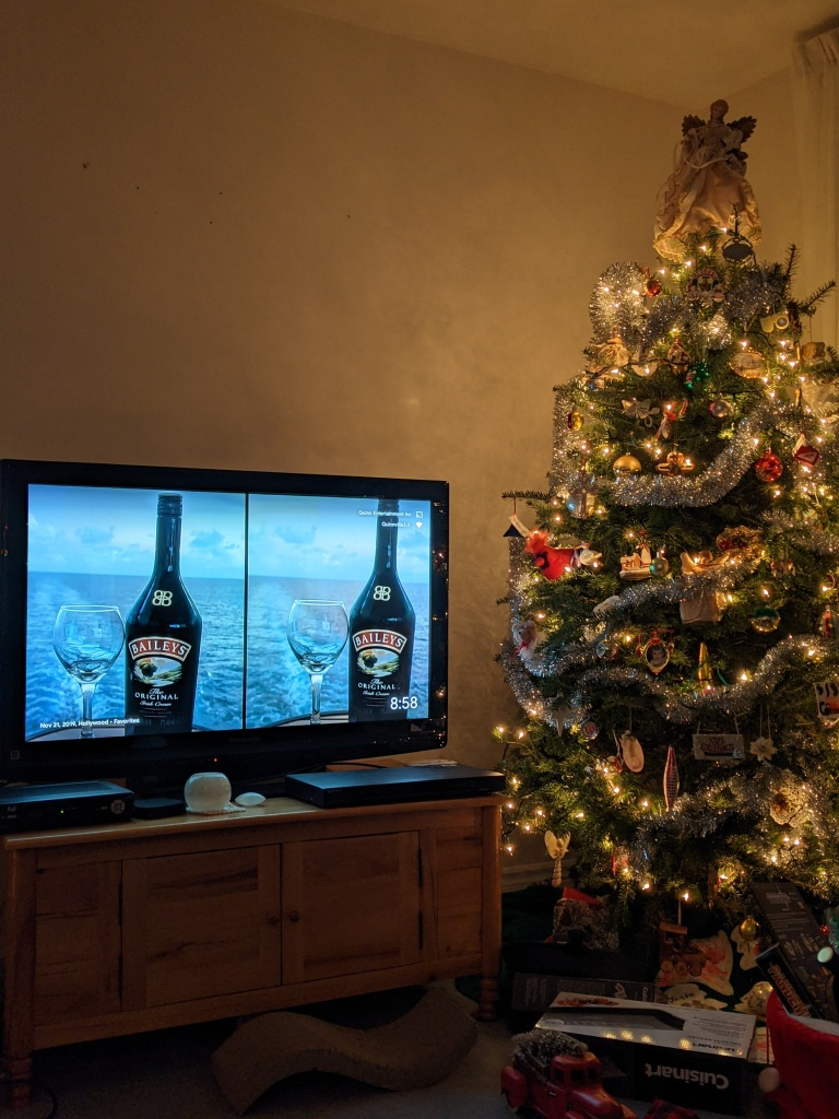 Christmas tree lit up beside a tv with a screen saver showing two photos of Bailey's Irish Cream and a wine glass with the ocean in the background. I took this on the balcony of my last cruise.