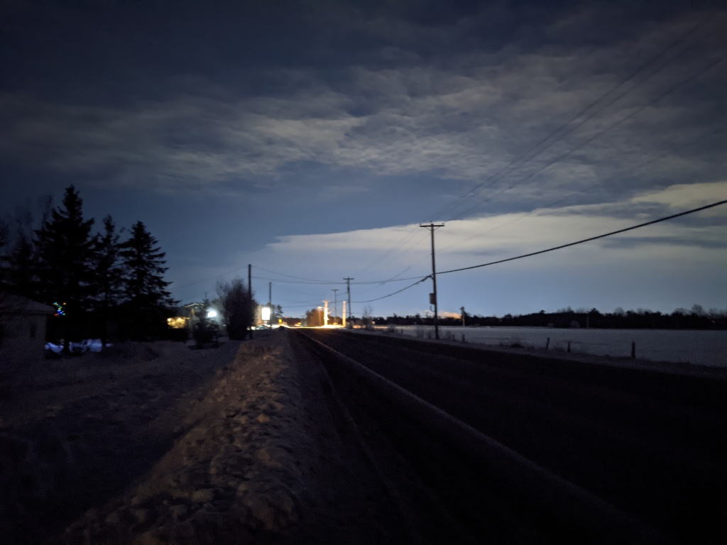 An empty street, partially cloudy sky, taken at night