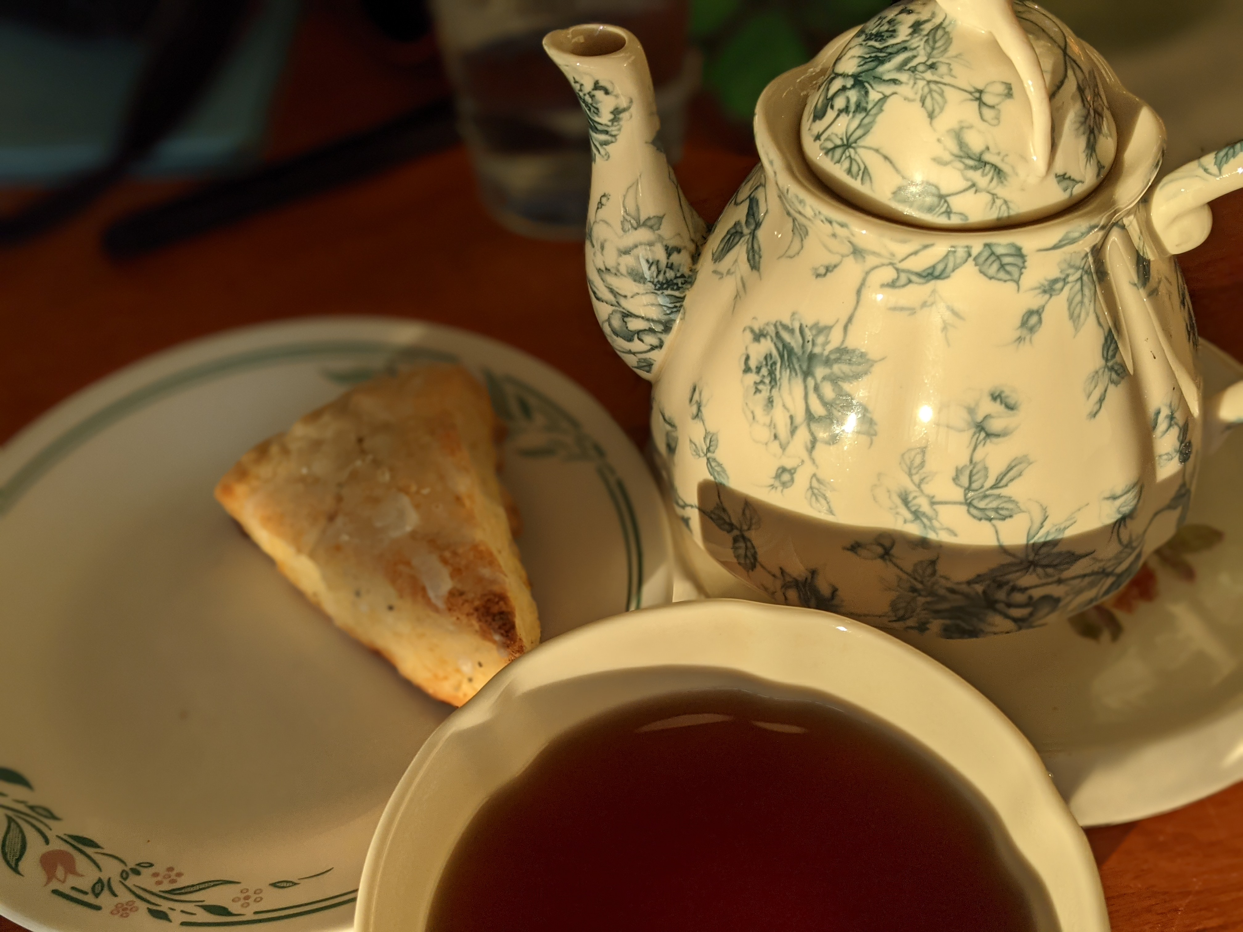 The warm glow of sunrise baths a teapot, teacup filled with tea and a scone