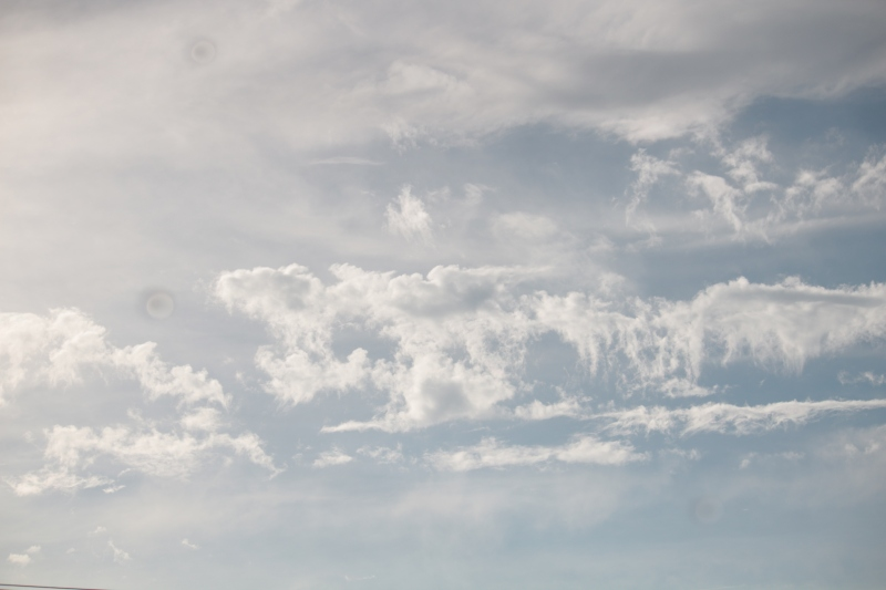 light blue sky with billowing white clouds floating by. Copyright WQuinn 2021